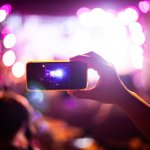 People taking photographs with smart phone during Live music concert and crowd in background