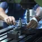 Worker operating industrial machine in metal workshop.