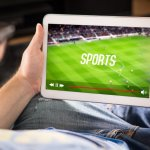 Man watching sports on tablet. Football and soccer game live stream and video player on screen. Pay per view (PPV) service. Replay or highlights broadcast. Lazy person relaxing.